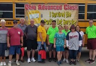 drivers in front of school bus with advanced class training banner