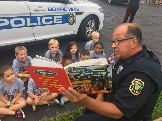 police officer reading a bus safety book to kindergarten students