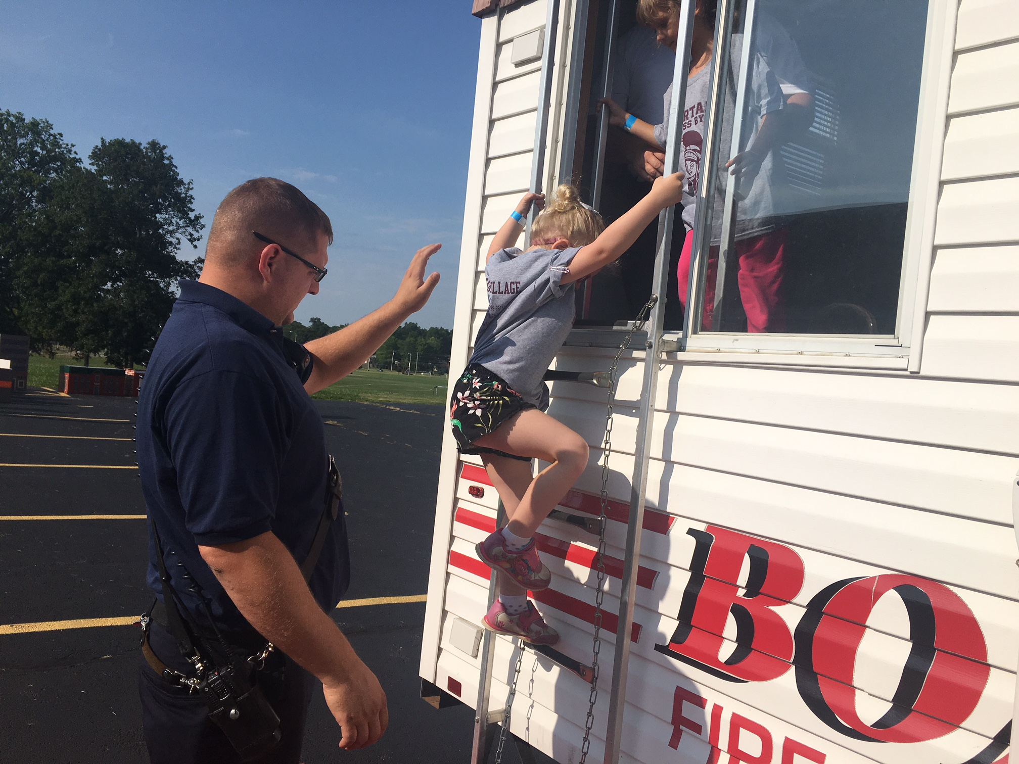 fire fighter helping student climb down ladder of mobile fire trailer