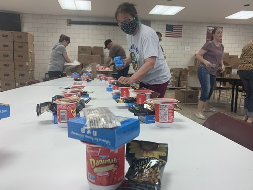Volunteers packing lunches with juice box, yogurt and chips