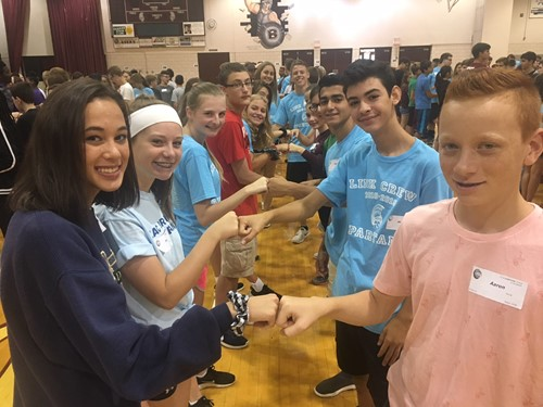 link leaders and high school freshmen fist bump in gym as part of icebreaker
