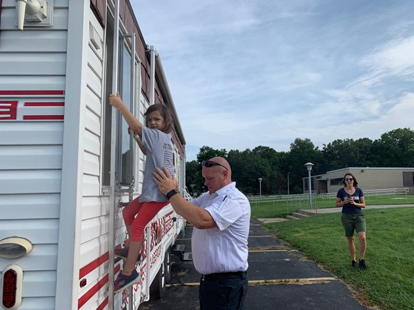 Firefighter helping kindergarten exit smokehouse window