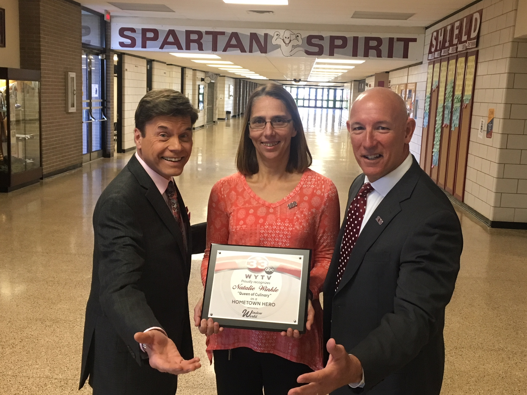 Natalie Winkle holding Home Town Hero Award with Channel 33 anchor Len Rome and Superintendent Tim Saxton