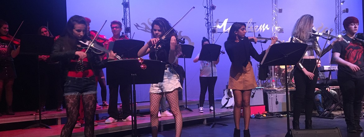 girls playing electric violins on stage for Project Mayhem concert