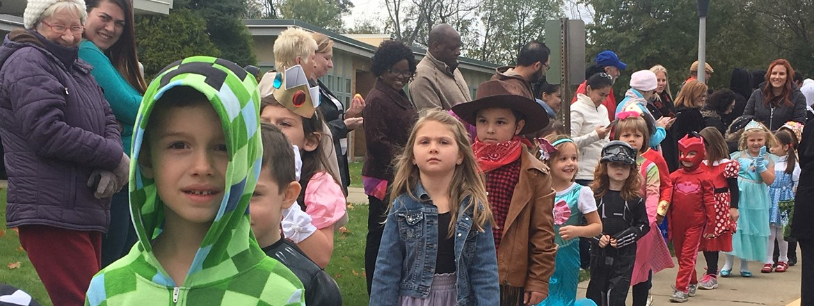 Costume parade outside with cowboys, mermaids, princesses with parents lining the sidewalk to watch.