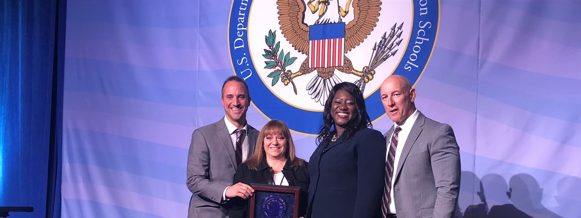 Superintendent Saxton, Principal Zoccali, Lisa Miller accepting national blue ribbon school award on stage in DC