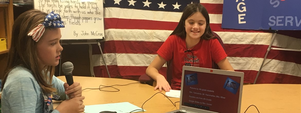 Students using microphone, computers, and cameras, did a live school wide broadcast on Veterans Day