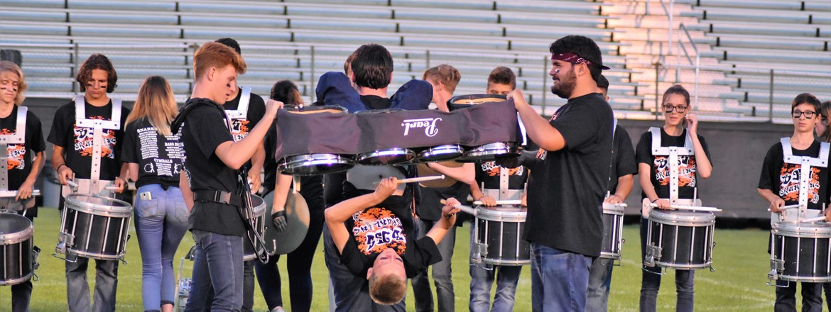 Drummer hanging upside by his knees, and playing a drumset that is held by two drum line members on the field during a Band Night performance.