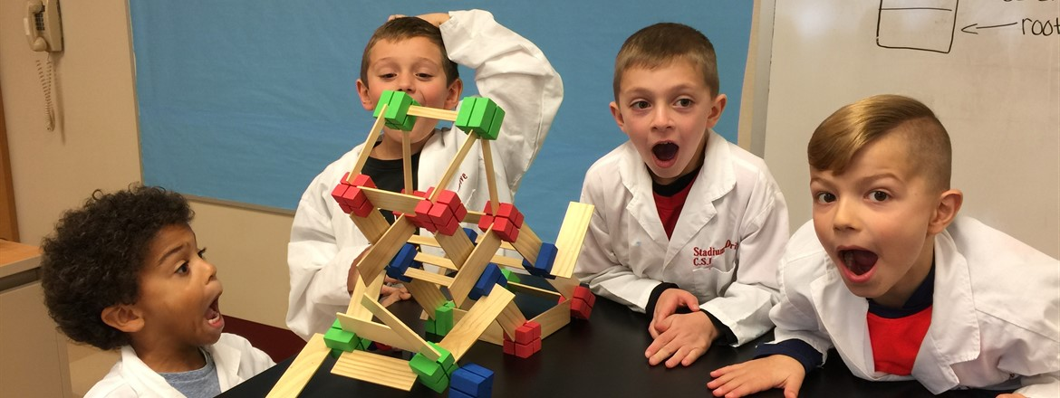 STEM Fridays, four first graders building a house with connecting wood and blocks are amazed it did not hold up when stressed.