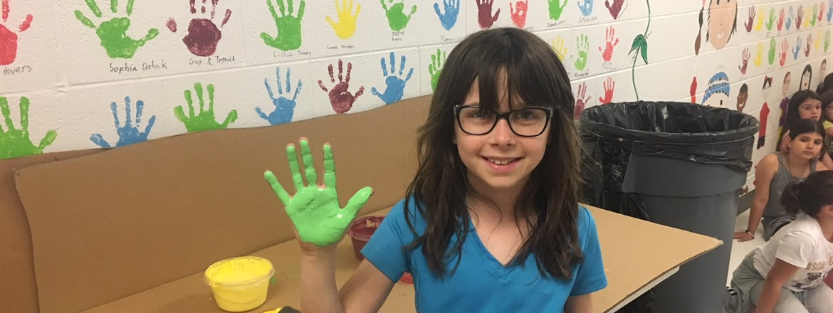 Girl with hand covered in green paint, ready to leave her print on the Wall of Fame