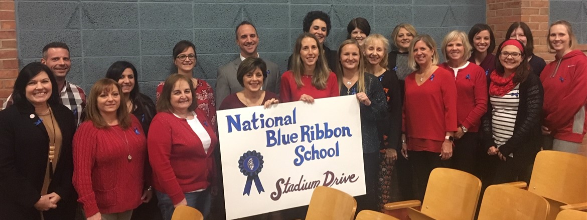 Teachers and Staff honored at Board of Education Meeting holding up National Blue Ribbon Schools Sign.