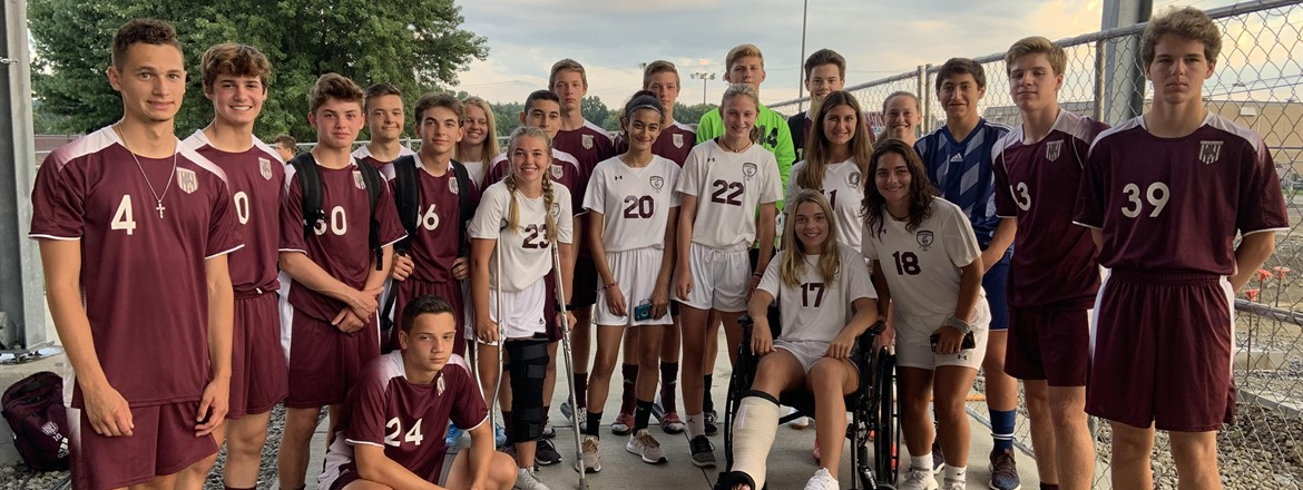 twenty two boys and girls in BHS soccer uniforms with at least one sibling each