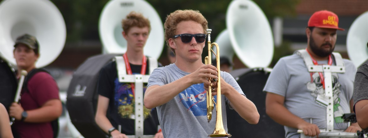 trumpet  player with tubas and drums behind on practice field