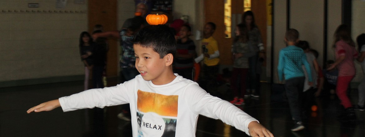 students balancing pumpkins on their heads in relay race