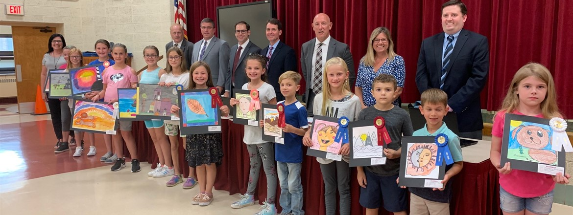 K-4 ribbon winners posing with art and standing in front of school board