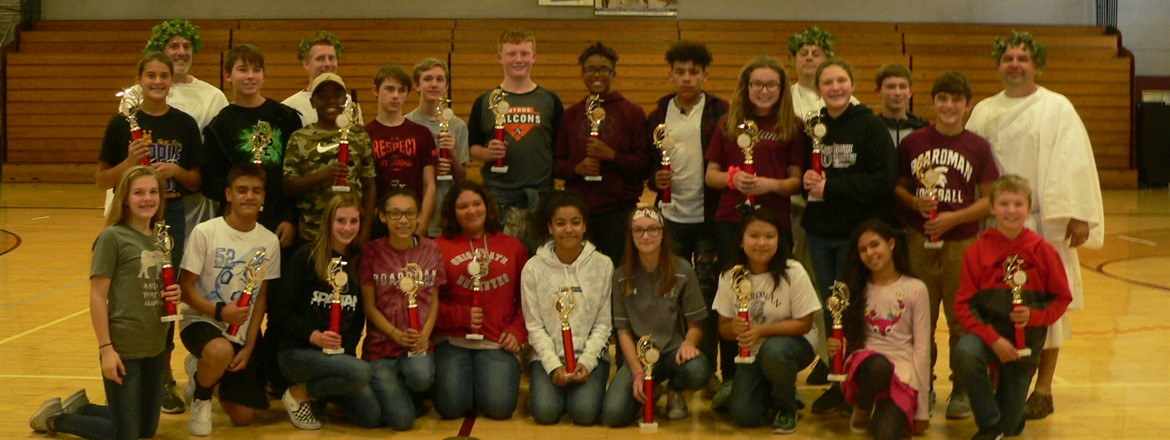 Winners of Greek Olympics with trophies in gymnasium