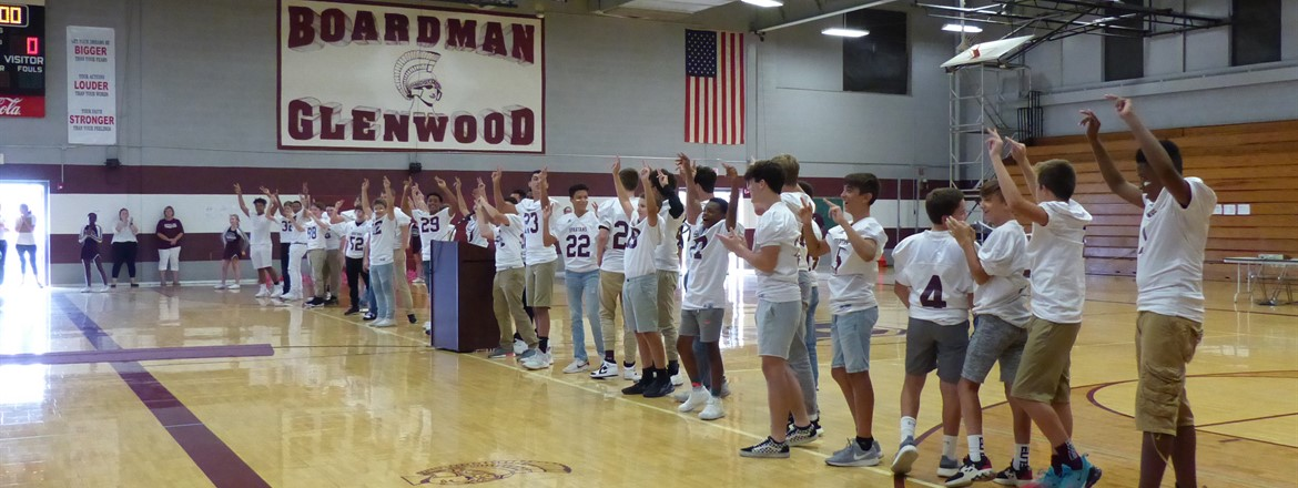 football players lined up in gymnasium for pep rally