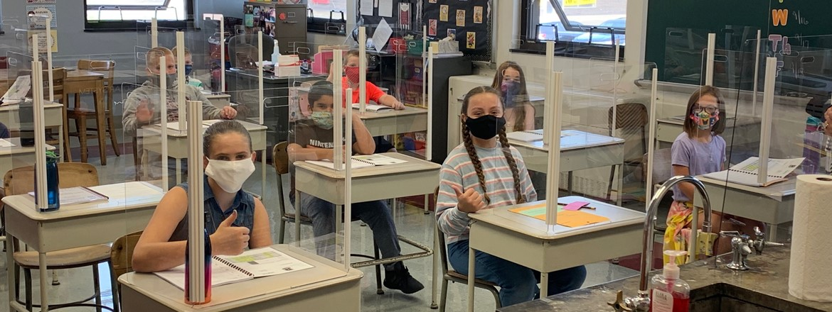 5th graders in masks at their desks with plexiglass shields