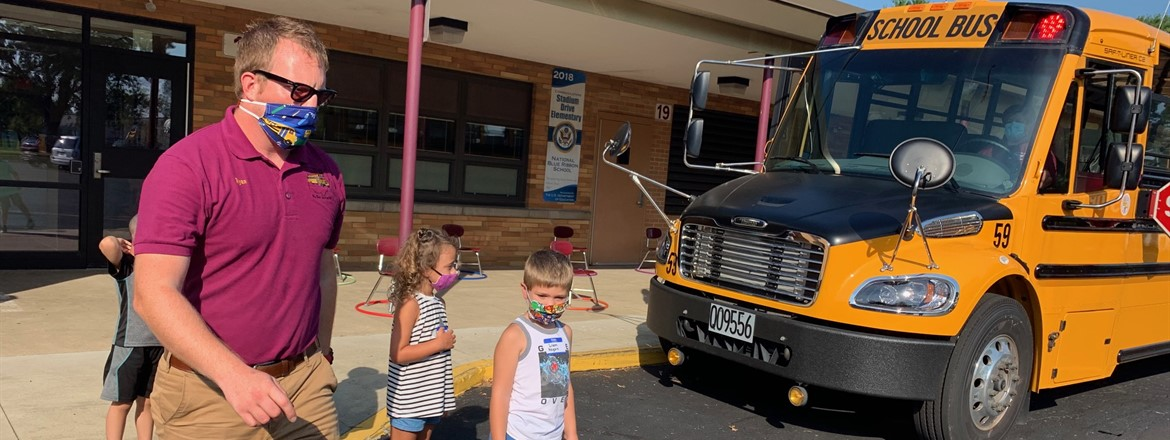 Transportation Director Ryan Dunn shows kindergarten how to cross in front of the bus