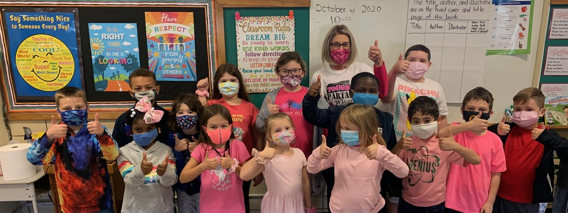 Mrs. Sutton's class dressed in pink with a thumbs up