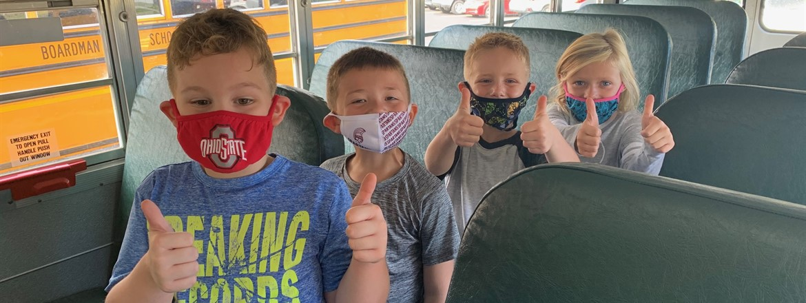four students smiling with thumbs up on board a school bus