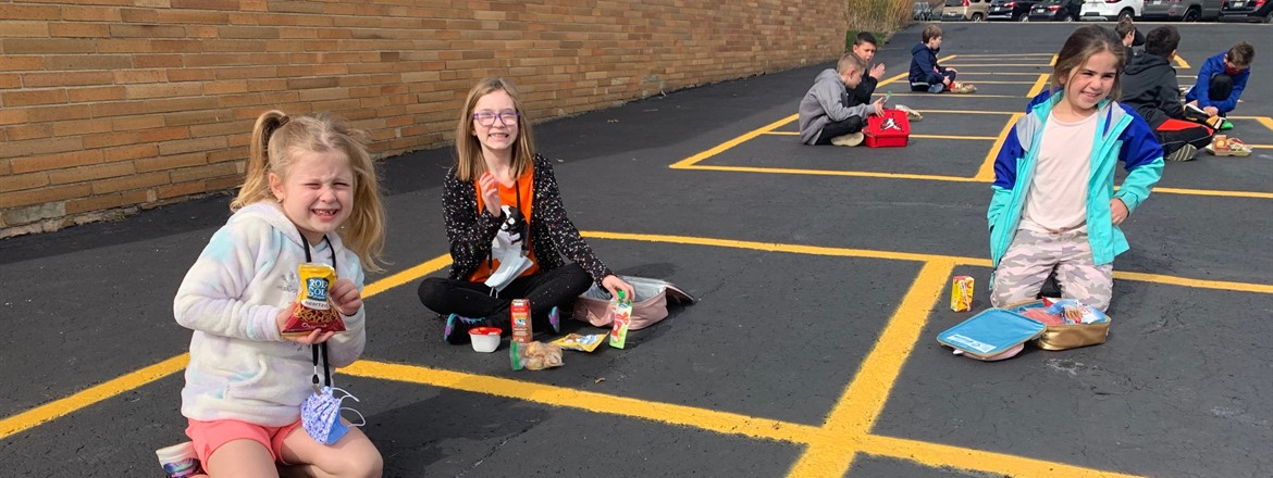 students eating on the parking lot squares outside
