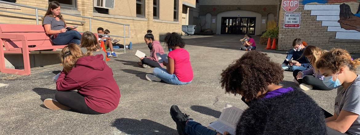 students reading and discussing a novel in the BCIS courtyard outside