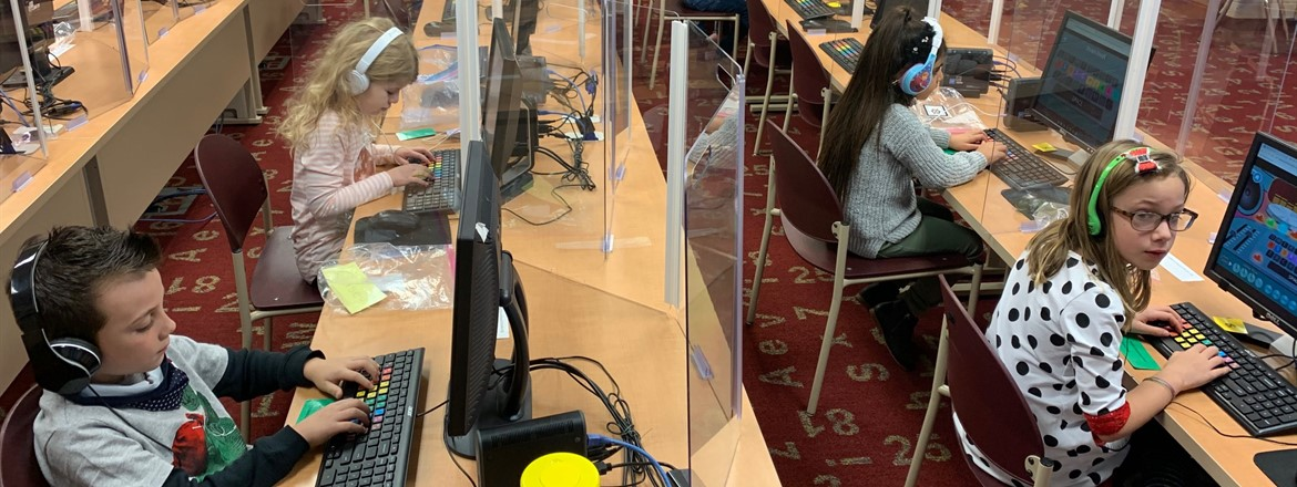 students learning keyboarding in computer lab with plexi glass stations