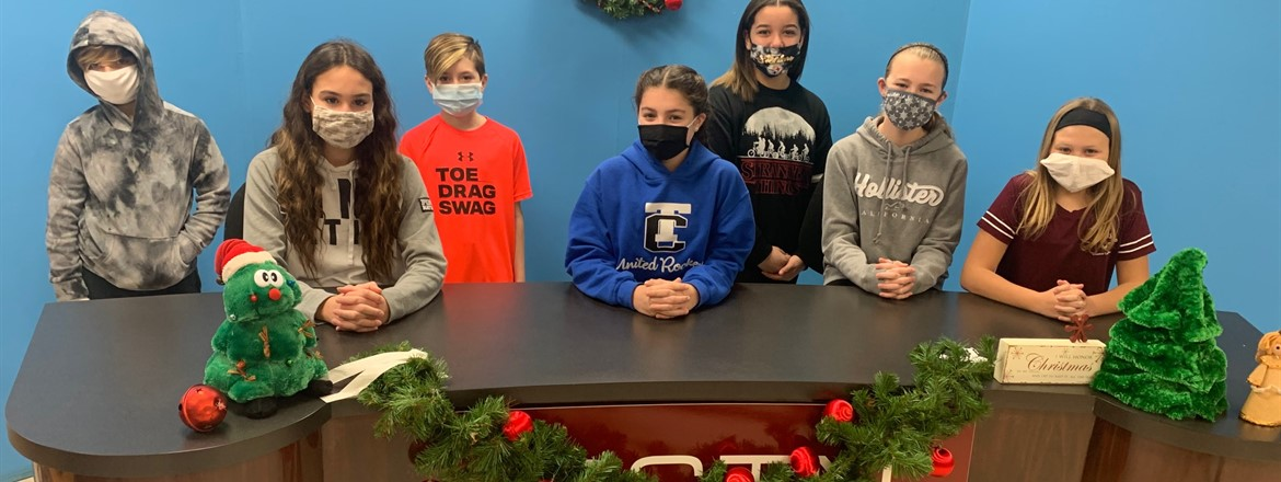 students in tv morning crew at anchor desk decorated for xmas