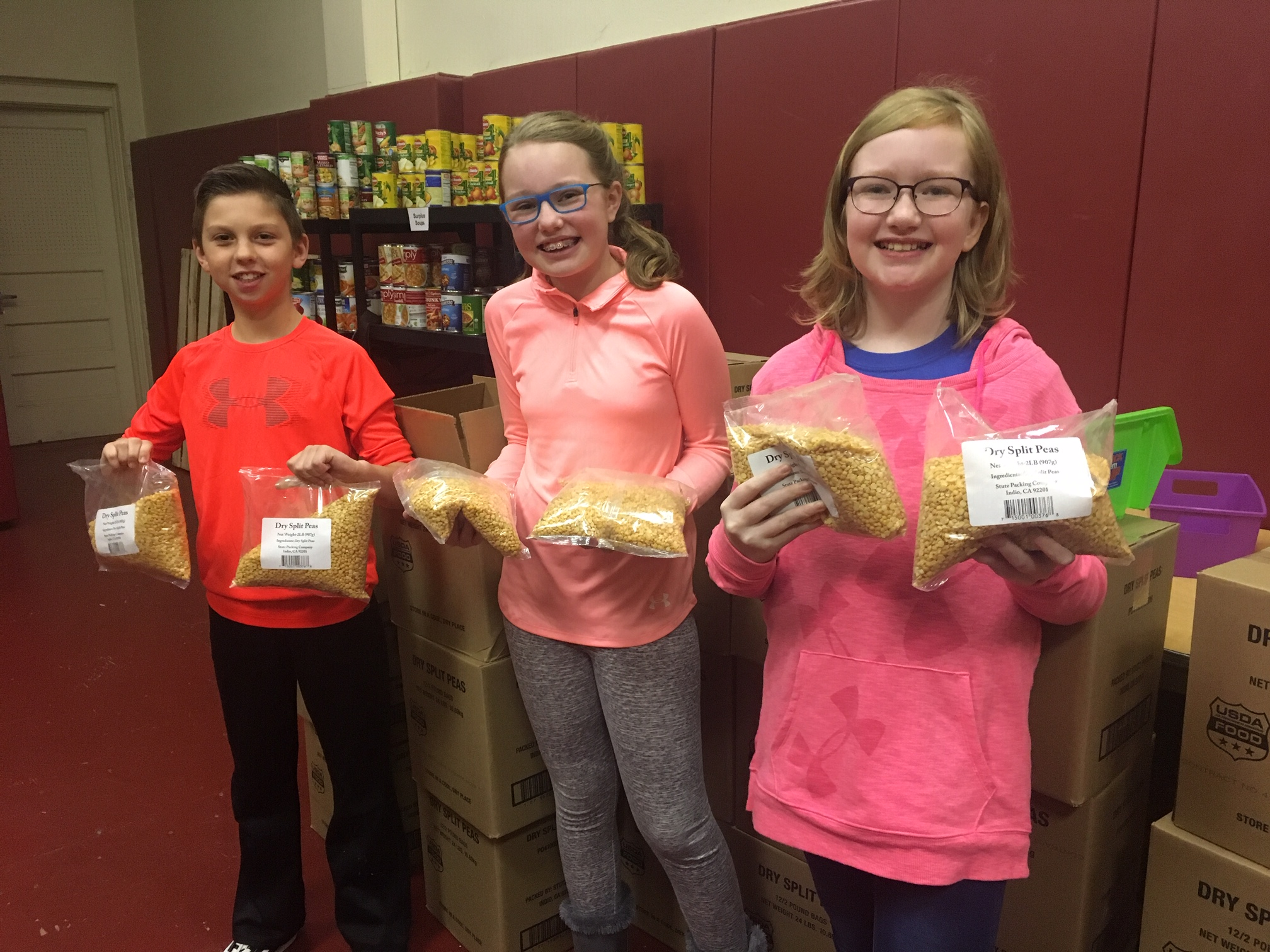 three students show bags of split peas used for recipes